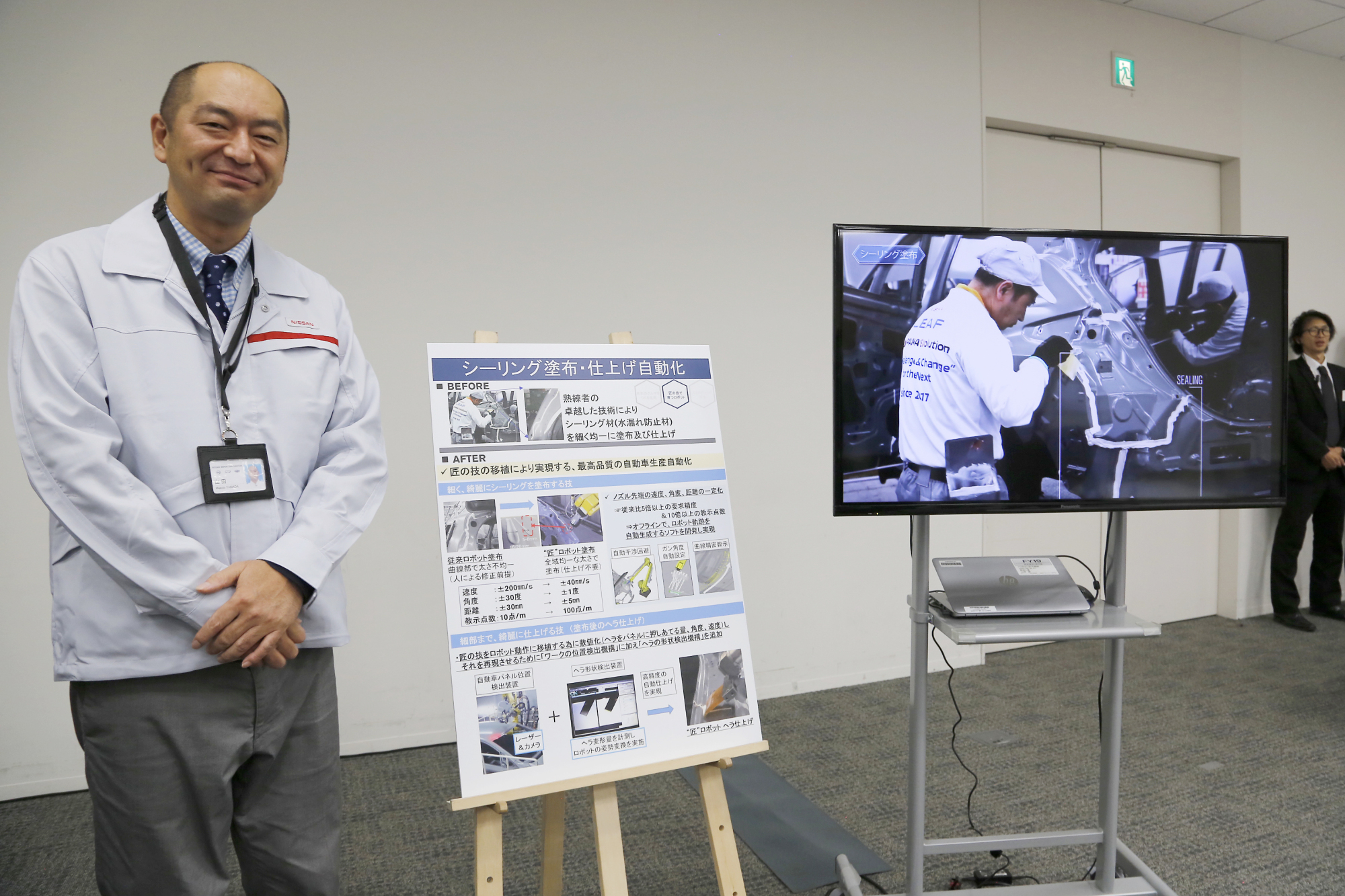 Engineer Makoto Yamada talks to reporters about using robotics for sealing as part of Nissan's new production methods at its intelligent factory during a news conference at the company's headquarters in Yokohama on Thursday. | AP