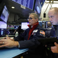 FILE — In this Nov. 20, 2019, file photo specialist Anthony Rinaldi (left) and trader Michael Urkonis work on the floor of the New York Stock Exchange.