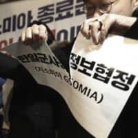 Protesters tear signs reading 'General Security of Military Intelligence Agreement between South Korea and Japan' during a rally demanding end of the pact, in front of the Japanese Embassy in Seoul on Thursday. | AP