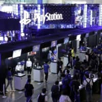 Attendees walk past the Sony PlayStation booth at the Tokyo Game Show 2019 in Chiba in September. | BLOOMBERG