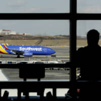 A Southwest Airlines jet moves on the runway as a person eats at a terminal restaurant at LaGuardia Airport in New York in January. Federal regulators have threatened to ground dozens of Southwest Airlines jets if the airline can't confirm that the planes, which it bought used from foreign operators, meet all safety standards. | AP