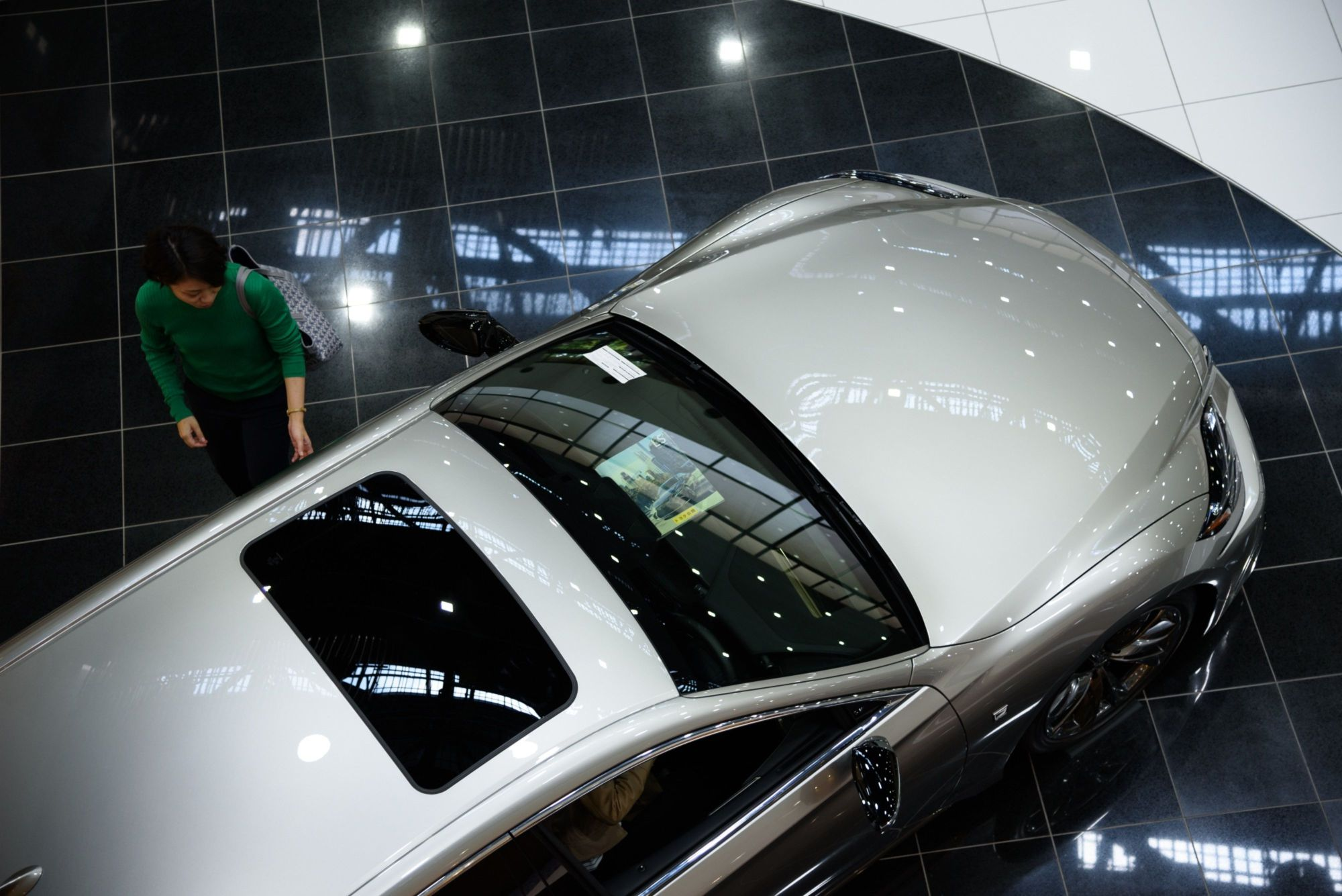 A visitor looks at a Toyota Motor Corp. Lexus LS 500h at the company's showroom in Toyota, Aichi Prefecture, in June. Toyota and weather information provider Weathernews Inc. have started tests to improve the accuracy of rain forecasts by using real-time data from windshield wipers on networked cars. | BLOOMBERG