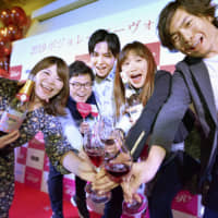 People celebrate at an event in central Tokyo early Thursday after Beaujolais Nouveau wine went on sale in Japan the same day. | KYODO