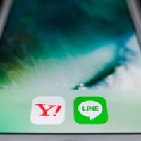 The icons for the Yahoo Japan and Line apps are displayed on a smartphone. | BLOOMBERG