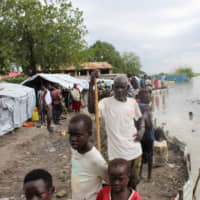 South Sudanese stand next to makeshift structures in the town of Pibor on Wednesday after heavy rains and floods forced hundreds of thousands of people to leave their homes. | REUTERS