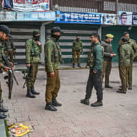 Security personnel stand near the site of a grenade blast at a market outside the campus of Kashmir's main university in Srinagar on Tuesday. | AFP-JIJI