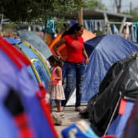 Central American migrants are seen in an encampment in Matamoros, Mexico, at the end of the Gateway International Bridge, where migrants sent back under the 'Remain in Mexico' program, officially called the Migrant Protection Protocols (MPP), await their U.S. asylum hearings in September. | REUTERS