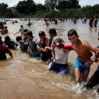 Migrants, part of a caravan traveling to the U.S., make a human chain to pull people from the river between Guatemala to Mexico in Ciudad Hidalgo and continuing to walk in Mexico last fall. | REUTERS