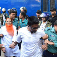 Police escort Islamist extremists accused of allegedly plotting the Holey Artisan Bakery cafe attack, carried out by Islamist militants, to a courtroom for their trial in Dhaka on Wednesday. Seven Islamist extremists were sentenced to death over a savage 2016 attack that killed 22 people, including 18 foreigners, at a Dhaka cafe popular with Westerners. | AFP-JIJI