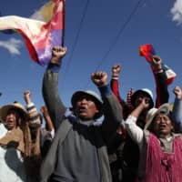 Supporters of former President Evo Morales stand at a blockade along a road leading to the state-owned Senkata gas filling plant in El Alto, Bolivia, on Sunday. | AP