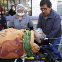 Paramedics transport a man injured during clashes with security forces to a hospital in El Alto, on the outskirts of La Paz Tuesday.   AP
