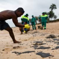 A resident works to remove an oil spill on Barra de Jacuipe beach in Camacari, Bahia state, Brazil, Oct. 22. | REUTERS