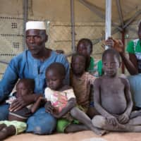 Zore Yusef sits with his family at an IDP camp in Pissila, Burkina Faso, Nov. 13. | VIA REUTERS