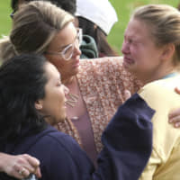 Students are comforted as they wait to be reunited with their parents following a shooting at Saugus High School that injured several people, Thursday in Santa Clarita, California. | AP