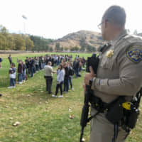 A police officer stands guard as students wait to be reunited with their parents following a shooting at Saugus High School that injured several people, Thursday in Santa Clarita, California. | AP