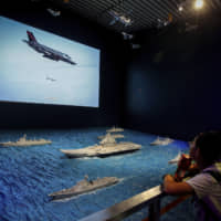 Visitors watch a TV screen showing a U.S. Air Force F-35 fighter jet firing a missile near models of China's Liaoning aircraft carrier with navy frigates and submarines on display at a military museum in Beijing on Aug. 1. | AP