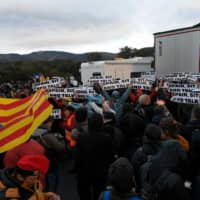 Protesters hold banners reading 'Spain sit and talk' as they block the AP-7 highway at the Spanish-French border in La Jonquera, northern Spain, on Monday during an action called by Tsunami Democratic movement for civil disobedience actions. | AFP-JIJI