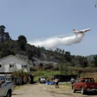 A DC-10 Air Tanker firefighting plane drops water to prevent a wildfire from spreading to homes near Concepcion, Chile, in February. | REUTERS