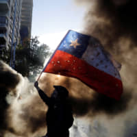 A demonstrator waves a Chilean flag during a protest against the government in Santiago Thursday.   REUTERS