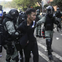 Riot police detain a protester at Hong Kong Polytechnic University on Nov. 18. As violent protests have roiled the city in recent months, Beijing has been managing its response from a villa on the outskirts of Shenzhen set up as a crisis command center, bypassing the formal bureaucracy through which it has supervised the financial hub for two decades.   AP