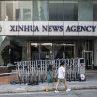 Pedestrians walk past a vandalized entrance to the offices of China's state-run Xinhua News Agency  in Hong Kong on Sunday, a day after protesters went on the rampage and vandalized the offices and some other buildings. | BLOOMBERG