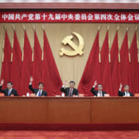 In this photo released by China's Xinhua News Agency, Chinese President Xi Jinping (center) and Politburo Standing Commitee members attend the fourth plenary session of the 19th Central Committee of China's ruling Communist Party in Beijing on Thursday. | AP