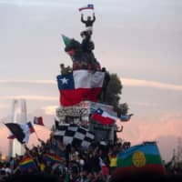 Chileans hold a 'Mourning March' in Santiago on Friday to protest the deaths of 23 people after more than 10 days of civil unrest that forced the government to abandon hosting two major economic and climate summits. | AFP-JIJI