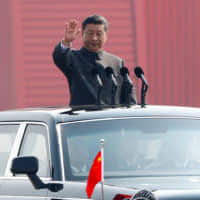 Chinese President Xi Jinping waves from a vehicle as he reviews the troops at a military parade marking the 70th anniversary of the founding of the People's Republic of China on Oct. 1. | REUTERS