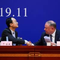 Yu Haibin, deputy director of China National Narcotics Control Commission, shakes hands with Austin Moore, an attache for the U.S. Department of Homeland Security and Immigration and Customs Enforcement, during a briefing in Xingtai, China, on Thursday. | AFP-JIJI