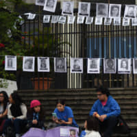 Photos of people who were forcibly 'disappeared' hang outside the Supreme Court building during a genocide case hearing in Guatemala City on Monday. | AFP-JIJI
