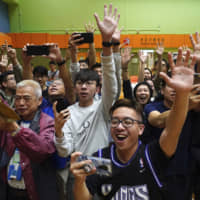 Supporters of pro-democracy candidate Angus Wong celebrate after he won in district council elections in Hong Kong on Monday | AP