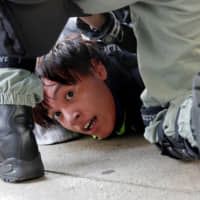 Police detain a protester in Hong Kong on Sunday. As anti-government protests stretch into their 23rd straight week, the city is being inundated with online rumors, fake news and propaganda from both sides of the political divide that's making it harder to resolve the crisis. | REUTERS