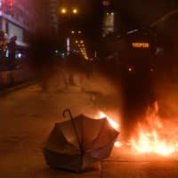 An umbrella is left on the road as fire burns in Hong Kong's Mong Kok district Saturday night. | AFP-JIJI