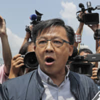 Pro-Beijing lawmaker Junius Ho attends a demonstration by police of an anti-riot vehicle equipped with water cannons at the Police Tactical Unit Headquarters in Hong Kong on Aug. 12. | AP