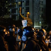 Protesters gather in front of the 'Goddess of Democracy' statue on campus after clashes with police at the Chinese University of Hong Kong (CUHK), in Hong Kong early Wednesday. Hong Kong pro-democracy protesters clashed with riot police in the city's upmarket business district and on university campuses Tuesday, extending one of the most violent stretches of unrest seen in more than five months of political chaos. | AFP-JIJI