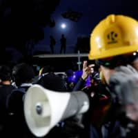 Anti-government protesters react during a standoff with riot police at the Chinese University of Hong Kong in Hong Kong Tuesday. | REUTERS