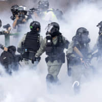 Police in riot gear move through a cloud of smoke as they detain a protester at Hong Kong Polytechnic University in the city on Monday. | AP