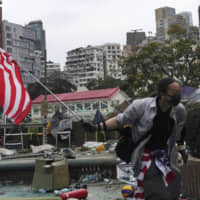 A protester holds an American flag at Hong Kong Polytechnic University on Wednesday. | AP