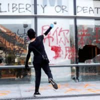 A protester throws a stone into a building at Hong Kong Polytechnic University on Nov. 11. | REUTERS