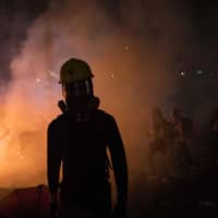 A protester walks amid tear gas and smoke from a burning barricade during clashes with police at the Chinese University of Hong Kong on Tuesday. | AFP-JIJI