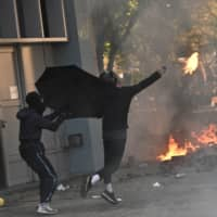A protester throws a Molotov cocktail after police fired tear gas outside Hong Kong Polytechnic University on Sunday. | AFP-JIJI
