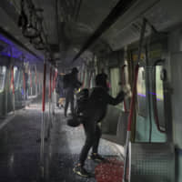 Pro-democracy protesters vandalize a train parked inside the Chinese University MTR station in Hong Kong on Wednesday. | AP