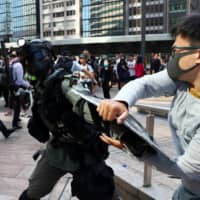 A protester scuffles with a riot police officer in Hong Kong's Central District on Wednesday. | REUTERS