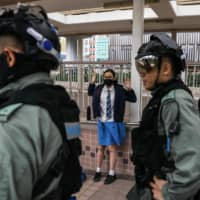 A student is questioned by police in the Sai Wan Ho district of Hong Kong on Monday following a day of pro-democracy protests. | AFP-JIJI