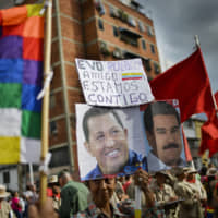A supporter of Venezuelan President Nicolas Maduro, whose image is held up at right, and the late President Hugo Chavez (left), carries the Spanish message: 'Evo. People. Friend. We are with you' during a rally in support of former Bolivian President Evo Morales, in Caracas Monday.   AP