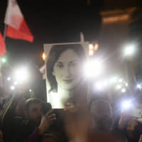 Protestors hold up pictures of slain journalist Daphne Caruana Galizia during a demonstration outside Malta's prime minister's office in Valletta Tuesday. | AP