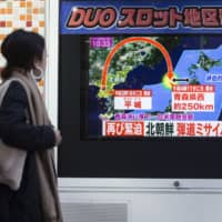 Passersby walk in front of a video monitor in Tokyo broadcasting news of a North Korean intercontinental ballistic missile test in November 2017. | BLOOMBERG