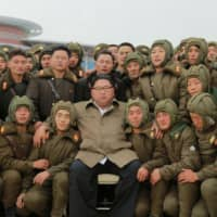 North Korean leader Kim Jong Un poses with sharpshooters of the Air and Anti-Aircraft Force in this undated picture released Monday. | KCNA / VIA REUTERS
