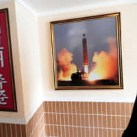 A man looks at a photo of the launch of a missile hanging on the wall of a factory workers' dormitory in Pyongyang.   AP