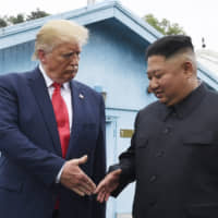 U.S. President Donald Trump and North Korean leader Kim Jong Un shake hands at the South Korean border village of Panmunjom in the Demilitarized Zone on June 30. | AP